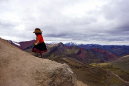 A young girl wanders alone up Rainbow Mountain